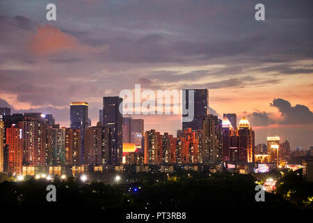High-rise buildings in Futian District illuminated at dusk. Shenzhen, Guangdong Province, China. - Stock Photo