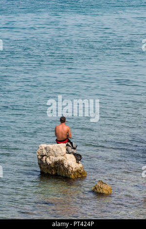 young man sitting on a rock fishing in the Mediterranean or Ionian sea on corfu in Greece. - Stock Photo