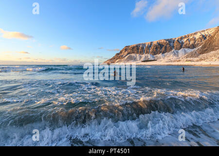 Surfers paddling, Unstad, Vestvagoy, Lofoten Islands, Norway - Stock Photo