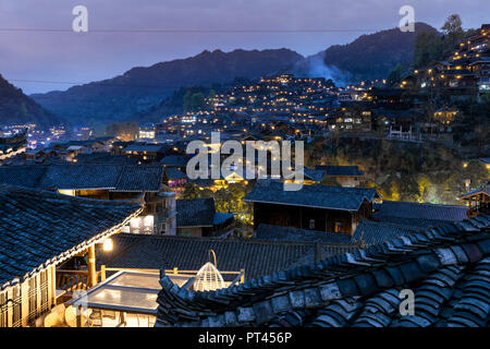 Xijiang Thousand Houses Miao Village at dusk, Guizhou, China - Stock Photo