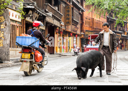 Man with pork, Xijiang Thousand Houses Miao Village, Guizhou, China - Stock Photo