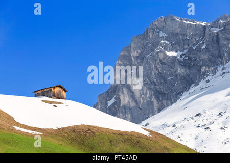 Typical hut during spring thaw in Partnun with Ratikon mountain range in the background, Partnun, Prattigau valley, District of Prattigau / Davos, Canton of Graubünden, Switzerland, Europe, - Stock Photo