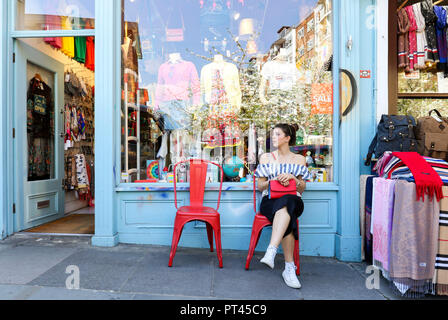 A girl sitting in Portobello Road, Notting Hill, London, United Kingdom - Stock Photo