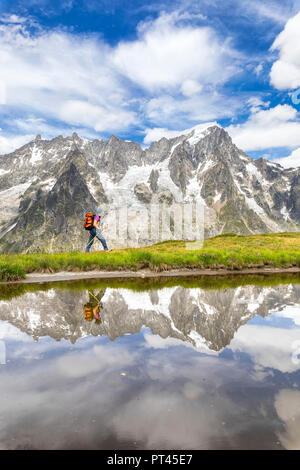 A trekker is walking on the Mont de la Saxe in front of Grandes Jorasses during the Mont Blanc hiking tours (Ferret Valley, Courmayeur, Aosta province, Aosta Valley, Italy, Europe) - Stock Photo