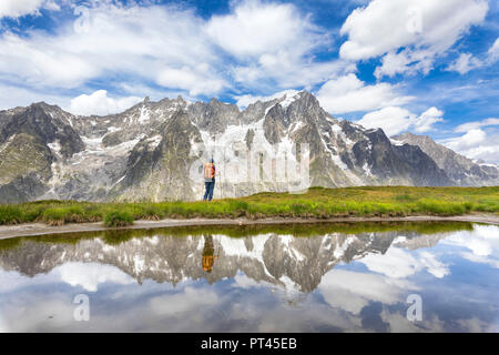 A girl is watching the Grandes Jorasses and the Mont Blanc Massif from the Mont de la Saxe during the Mont Blanc hiking tours (Ferret Valley, Courmayeur, Aosta province, Aosta Valley, Italy, Europe) - Stock Photo