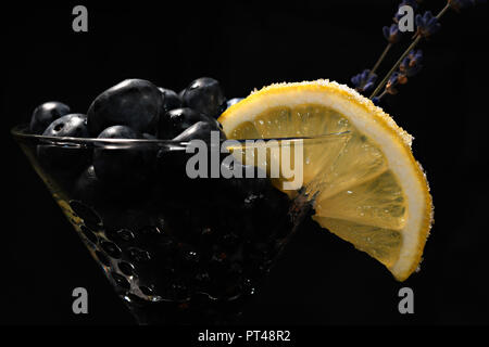 Cocktail with bluberriy in martini glass isolated on black background - Stock Photo