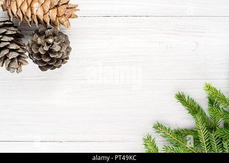Christmas 2019. Wooden white background with a frame of twigs and cones - Stock Photo