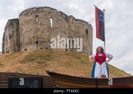 Female actress in costume (playing Mad Alice) giving live talk & performance on wagon in front of Cliffords Tower - York, Yorkshire, England, UK. - Stock Photo