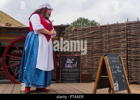 Female actress in historic costume & curly wig (playing Mad Alice) giving live talk & performance on stage, by wagon - York, Yorkshire, England, UK. - Stock Photo