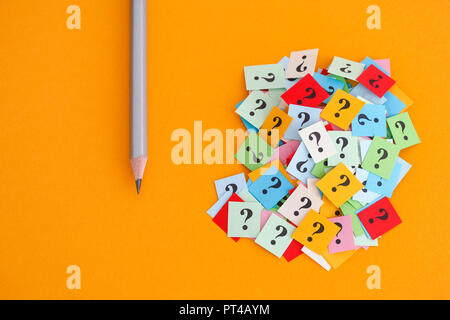 Pencil and question marks on yellow background. Concept image. Close up. - Stock Photo