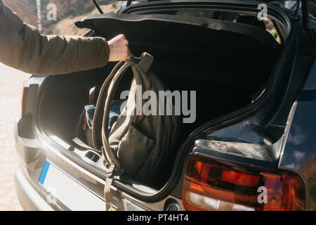 A man or a tourist puts a backpack in the trunk of a car. Preparation for the trip. The concept of tourism or travel by car. - Stock Photo