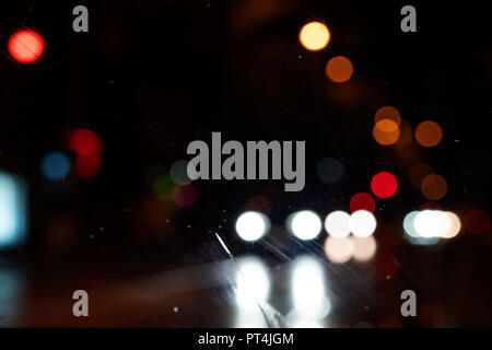 Blurred light from car headlights reflected from a wet road on a rainy night. Shot through the windshield. - Stock Photo