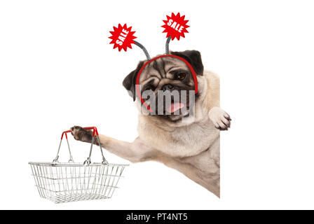 happy smiling pug puppy dog, holding up shopping basket, wearing diadem with red sale sign, isolated on white background - Stock Photo