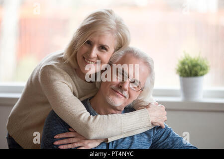 Smiling caring middle aged wife embracing senior husband at home, happy old woman hugging loving mature man looking at camera, retired elderly family  - Stock Photo