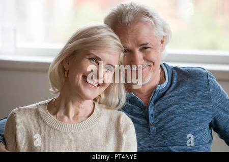 Headshot portrait of happy middle aged romantic couple dating posing indoors, smiling retired old family embracing looking at camera, loving senior ma - Stock Photo