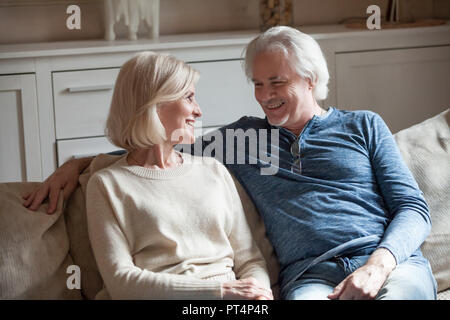 Happy loving senior couple talking looking in eyes relaxing on sofa together, elderly middle aged family embracing having fun enjoying conversation at - Stock Photo