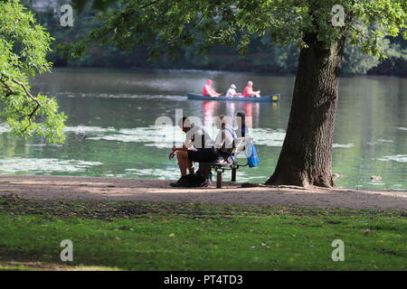 three people resting on a bench next to the Alster - Stock Photo