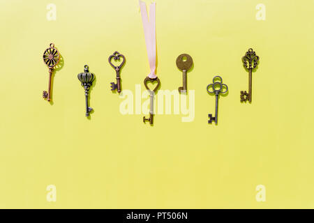 Bunch of keys, steel house keys on yellow background.a lot of different keys isolated.Valentines unlock love concept.Copy space - Stock Photo