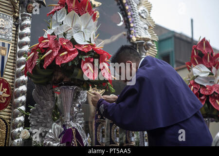 "Lima, Peru. 6th October 2018. Devotees participate in a procession of the Lord of the Miracles most know as ""El Señor de los Milagros"" in Lima Peruvian capital. Every October for the past four centuries this procession takes place in Lima and is known as the most important religious event in Peru. This Peruvian tradition commemorates the devastating 1746 Lima earthquake which left only a mural of Christ standing in a city area. Credit: SOPA Images Limited/Alamy Live News - Stock Photo"
