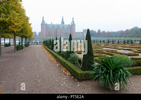 Frederiksborg Castle and the Baroque Garden in Hillerød, North Sealand, Denmark, on a foggy autumn day - Stock Photo