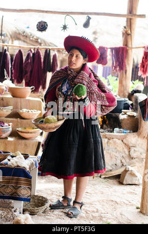 Chinchero, Peru - Sep 15, 2016: A young woman in traditional clothing explains the knitting process which includes the dyeing of alpaca and sheep wool - Stock Photo