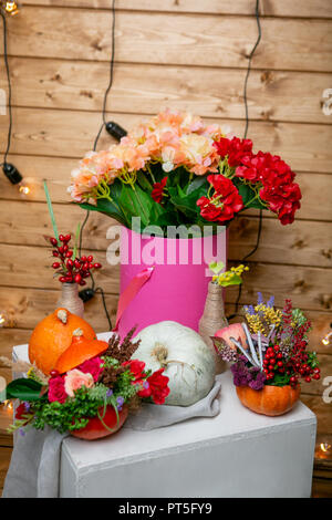 still life with flower arrangements in pumpkins and hydrangea in a box - Stock Photo