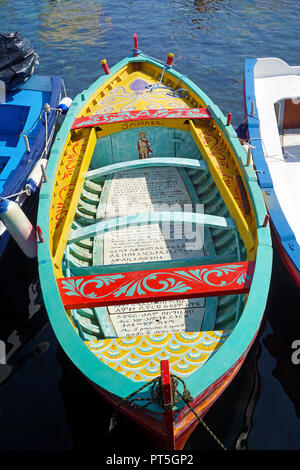 Colourful painted fishing boat with religious text at harbour of fishing village Aci Trezza, comune of Aci Castello, Catania, Sicily, Italy - Stock Photo