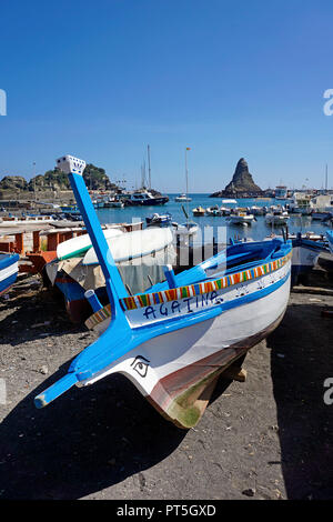 Fishing boats at harbour of fishing village Aci Trezza, behind the Faraglione grande, cyclops islands, comune of Aci Castello, Catania, Sicily, Italy - Stock Photo