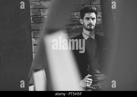 Attractive man in the street wearing british elegant suit. Young bearded businessman with modern hairstyle in urban background. Black and white photog - Stock Photo
