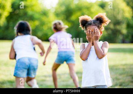 Girls playing hide and seek game in park. - Stock Photo