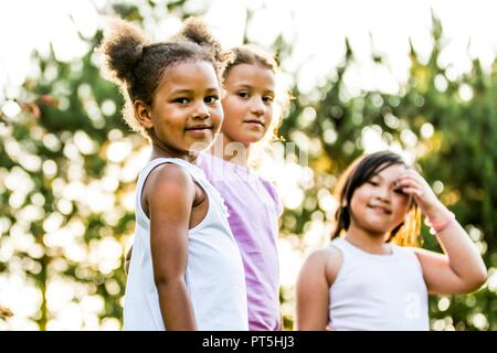 Portrait of girls smiling together in park while playing. - Stock Photo