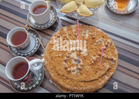 Hazelnut milk cake . Delicious cakes with hazelnut on wooden glass table . Black tea in glass cup on the table . Azerbaijan tea in traditional glass on tray closeup - Stock Photo