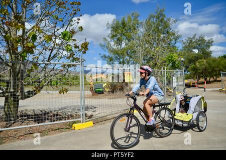 Woman riding a bicycle with a bicycle trailer for children, Townsville, QLD, Australia