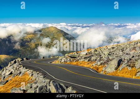 Winding road descending from Mount Washington, NH on a sunny autumn afternoon. Mount Jefferson peak stands above a thick layer of fluffy clouds. - Stock Photo