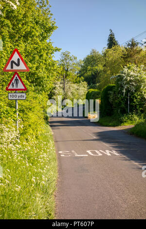 Warning triangle road signs for bends and pedestrians with slow sign on a British country lane, Sharpenhoe, UK - Stock Photo