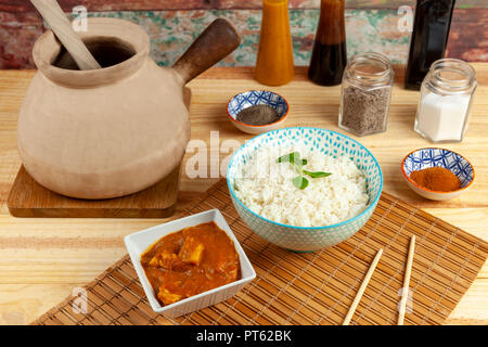 Bowl of rice and a portion of chicken curry laid out on a bamboo mat along side a traditional Chinese cooking pot and condiments on a wooden table - Stock Photo