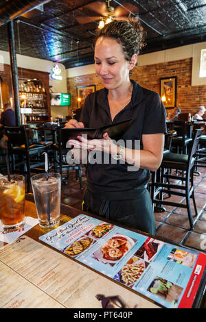 Lakeland Florida Harry's Seafood Bar & Grille restaurant interior woman waitress writing order employee working - Stock Photo