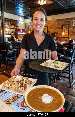 Lakeland Florida Harry's Seafood Bar & Grille restaurant interior waitress server serving calamari bowl gumbo soup employee working lunch plates - Stock Photo