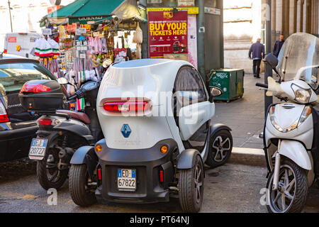 Renault Twizy electric vehicle car parked in a small space between scooters in the centre of Rome,Italy - Stock Photo
