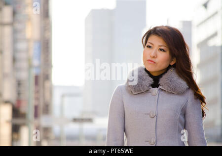 Japanese Girl poses on the street in Ginza, Japan. Ginza is a shopping city located in Tokyo. - Stock Photo