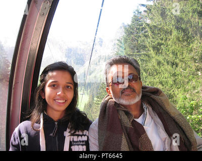 FATHER AND DAUGHTER IN CABLE CAR TO MOUNT TITLIS, SWITZERLAND - Stock Photo