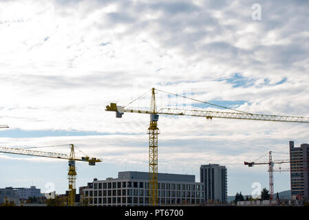 a view of the roofs of the German city, the cranes and the construction site of new offices and houses - Stock Photo