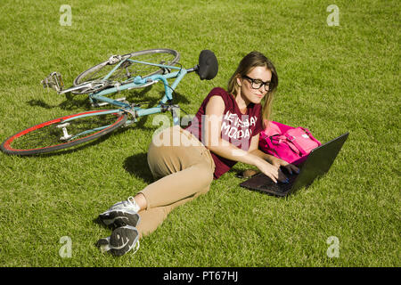 Pretty student woman wearing glasses lying on the green grass with open laptop near her bike and pink backpack, she writting her exam tests - Stock Photo