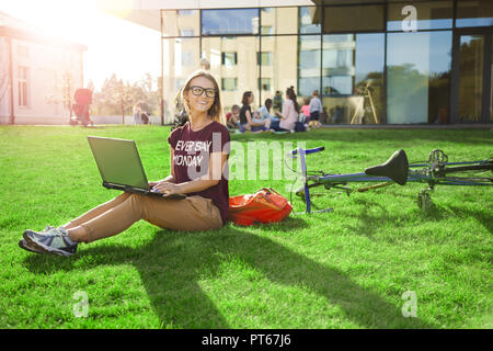 Confident student woman wearing glasses sitting on the green grass near the bike and backpack and doing her exam tests - Stock Photo