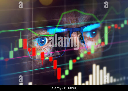 Close up of stock market trader looking at graph of share prices - Stock Photo