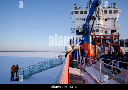The Icebreaker ship trapped in ice tries to break and leave the bay between the glaciers - Stock Photo
