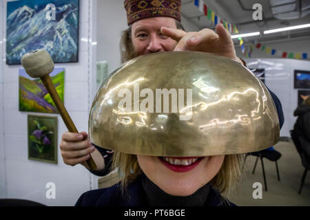 Using the Tibetan singing bowl during a sound therapy session at the Nepal Culture Festival in Moscow, Russia - Stock Photo