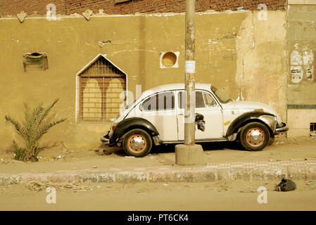 Old black and white Volkswagen Beetle parked on the side walk of a street of Aswan, Egypt. - Stock Photo