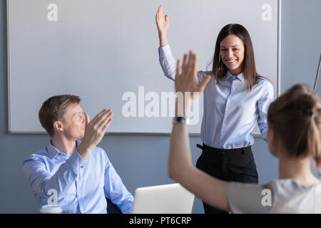 Business people and female team leader raising hands expressing  - Stock Photo