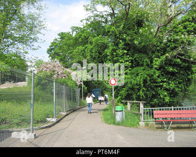TOURISTS WALKING ON PATHWAY ALONG THE BANKS OF THE RHINE RIVER, SWITZERLAND - Stock Photo